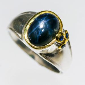 Δαχτυλίδι σε ασήμι 925 με κίτρινο και λευκό επιχρύσωμα στα 14Κ με star Ζαφείρι σε οβάλ καμπουσόν κοπή sta 6.50 ct και τρία μπλε Ζαφείρια στα 0.24 ct από την Αφρική (ΚΩΔ 9679Α)