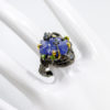 Δαχτυλίδι σε ασήμι 925 με μαύρο και κίτρινο επιχρύσωμα στα 14Κ με σκαλιστό Τανζανίτη στα 8.00 ct, Sky Blue Τοπάζια στα 0.40 ct και Χρωμοδιοψίδιους στα 0.40 ct. Με προελεύσεις λίθων από την Τανζανία, Βραζιλία και την Ρωσία (ΚΩΔ 9616Α)