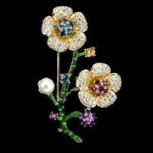 Καρφίτσα σε ασήμι 925 με κίτρινο επιχρύσωμα στα 18Κ και πράσινα σμάλτα. Το κόσμημα περιέχει φυσικούς πολύτιμους και ημιπολύτιμους λίθους όπως τα London Blue Τοπάζια, οι Ροδολίτες Γρανάτες, οι Αμέθυστοι, το F/W Pearl και o Κιτρίνης Χαλαζίας, το συνολικό βάρος των λίθων είναι στα 3.20 ct και οι προελεύσεις των λίθων είναι η Βραζιλία, η Μοζαμβίκη και η Ιαπωνία (ΚΩΔ 5369Α)