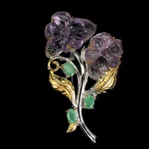Χειροποίητη καρφίτσα σε ασήμι 925 με λευκό και κίτρινο επιχρύσωμα στα 14Κ με δύο σκαλιστές Αμετρίνες σε σχήμα Λουλουδιών στα 32.66 ct και τρία Σμαράγδια σε κοπή οβάλ στα 3.00 ct Οι προελεύσεις των λίθων είναι από την Βολιβία και την Βραζιλία (ΚΩΔ 6248Β)