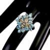 Δαχτυλίδι σε ασήμι 925 με λευκό επιχρύσωμα στα 14Κ με δέκα τέσσερα γαλάζια φυσικά Ζιρκόνια στα 12.60 ct και τέσσερα Σαμπανί/χρυσό φυσικά Ζιρκόνια στα 4.60 ct από την Καμπότζη (ΚΩΔ 6726Β)